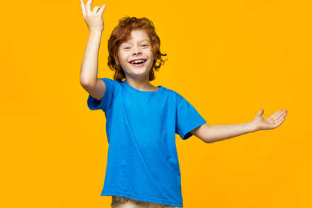 redheaded boy blue t-shirt yellow background freckles and fun laugh gesture with your hands
