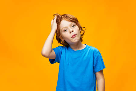 boy red hair blue t-shirt yellow isolated background freckles and surprised look dazed look