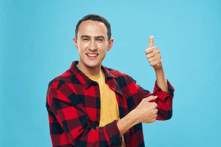 A man in a plaid shirt shows with his hand a thumb up fun 免版税图像