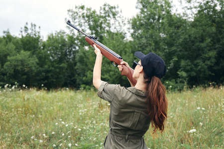 Military woman holding gun up sight hunting back view fresh air green