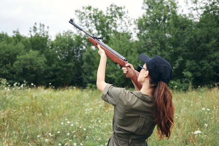Military woman holding gun up sight hunting back view black cap