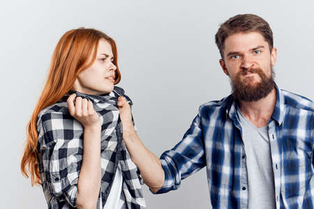 young couple in plaid shirts conflict communication relationship light background