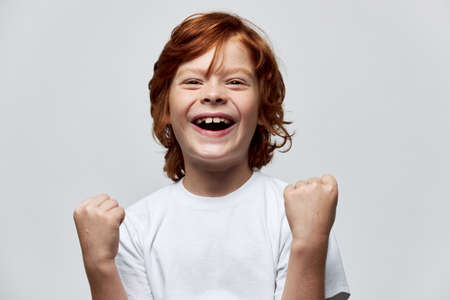 Cheerful red-haired boy gesturing with his hands smile childhood joy