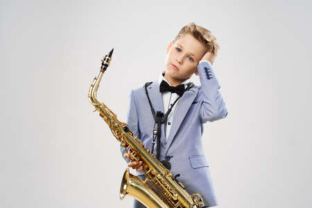 Boy musician in a suit plays the saxophone