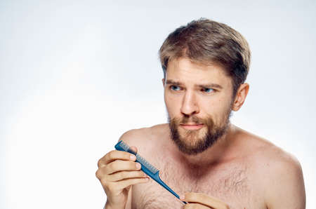 A man with a comb in his hands caring for a beard shoulders
