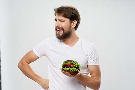Man with hamburger fast food diet food intake white t-shirt
