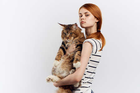 Red-haired woman holds in her hand a cat striped T-shirt light background home pet