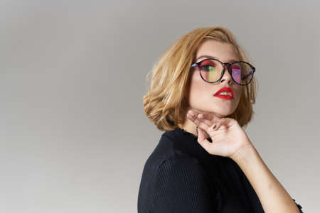 Blonde girl with glasses red lips black blouse cropped view glamor light background studio