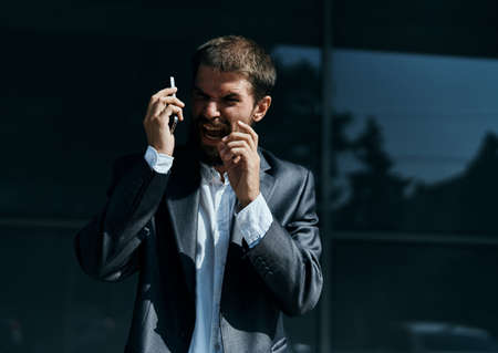 Business man communicates on the phone outdoors emotions executive manager lifestyle