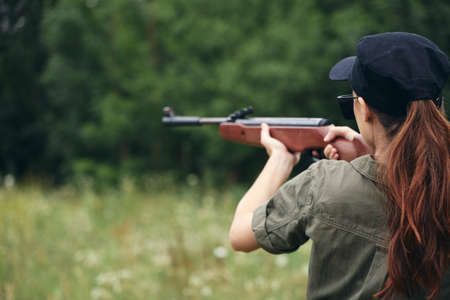 Woman on outdoor weapon in hand sight hunting nature fresh air