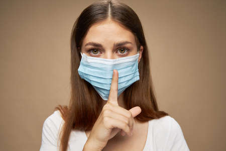 Women in medical mask and forefinger confident look Stockfoto