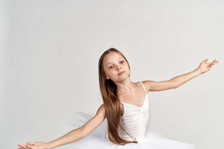 girl ballerina in white costume pointe shoes tutu dance light background cropped view