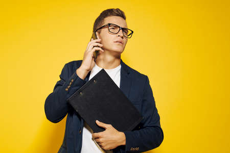 business man at work wearing glasses and a jacket on a yellow background talking on the phone employee model Standard-Bild