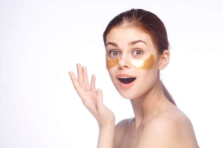 woman cares for face skin patches under the eyes cosmetology naked shoulders emotions model