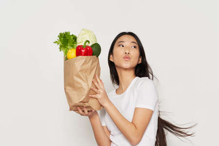woman with a package of groceries vegetarian healthy Stok Fotoğraf
