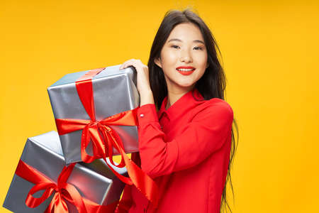 Woman with gifts Asian appearance red shirt holiday birthday