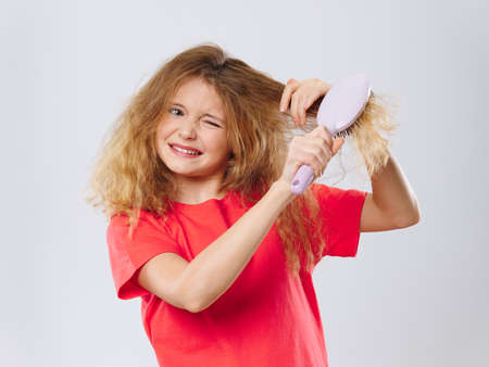 girl with difficulty combing her hair red t-shirt close-up