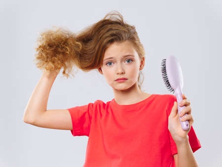 Girl holding a comb hair care close-up red T-shirt Banque d'images