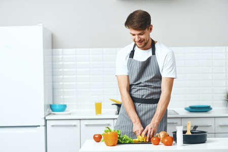 male chef in gray clip art are cutting vegetables on the kitchen board Stock Photo