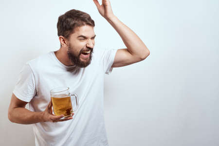 man with a mug of beer in his hands and a white t-shirt light background mustache beard emotions model