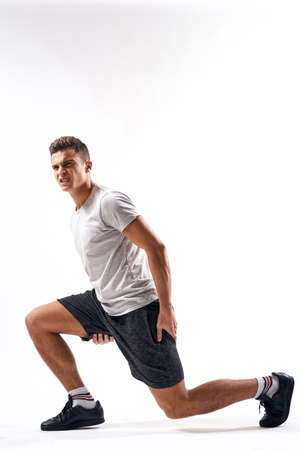 A sports man in shorts and a full-length T-shirt does exercises on a light background Stock fotó