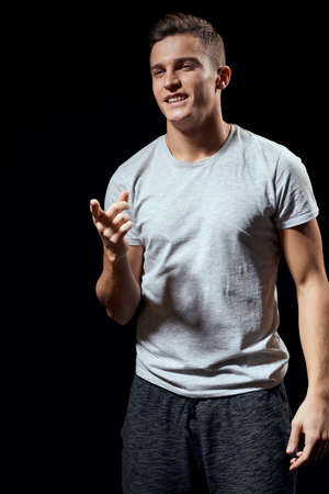 handsome man in white t-shirt on black background inflated arm muscles sport model cropped view Copy Space