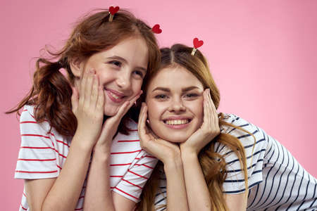 Cheerful mom and daughter lifestyle joy striped shirts family pink background Archivio Fotografico