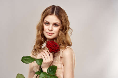 Portrait of a beautiful woman with a red rose on a beige background cropped view of an evening dress