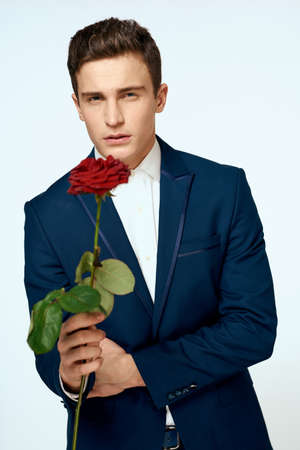 A man in a suit with a rose in his hands a gift date light background Foto de archivo
