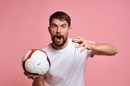 Man with a soccer ball on a pink background energy gesticulate with his hands coach emotions model