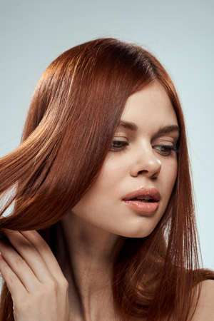 pretty redhead woman holding her hair with hands grooming shoulders light background Stock fotó