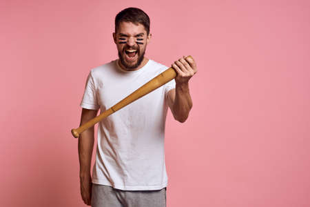 Emotional man with a baseball bat in his hand on a pink background and black lines on the face of the model grimace