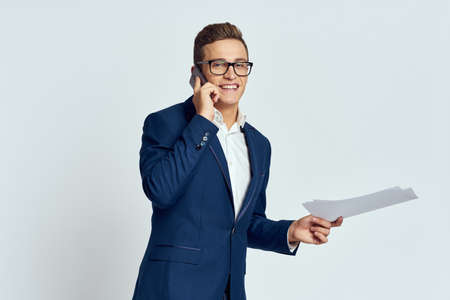 Business man in a suit talking on the phone with glasses with documents technology official