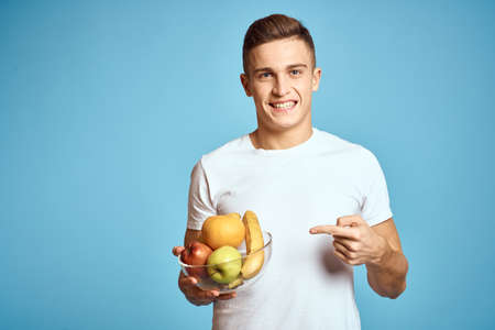 Happy man with fresh fruits gesturing with hands blue background white t-shirt vitamins bananas oranges apples