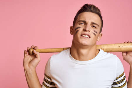 Energetic man with a bat on a pink background T-shirt face make-up black lines aggression model Stock fotó