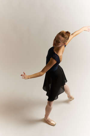 Ballerina in pointe shoes and in a tutu on a light background dance correct positioning of the legs slim figure