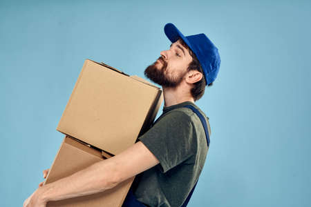 Man in working uniform with boxes in hands delivery service blue background