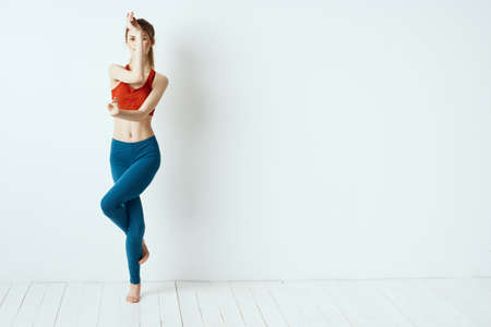 Sportive woman pose gymnastics balance exercise light background
