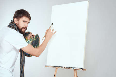 Male artist paints on easel palette art creativity light background