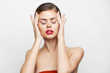 woman with bare shoulders With closed eyes, red lips are holding onto the face body care