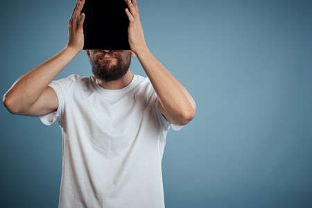 man covered his face with a tablet on a blue background in a white t-shirt Stock fotó