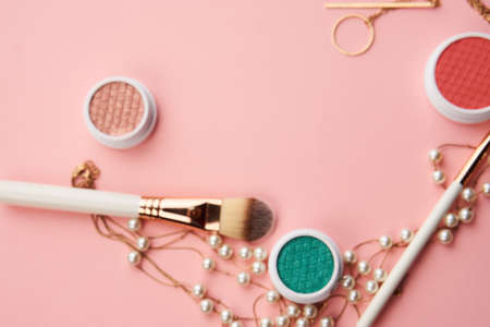 makeup brushes and eyeshadow professional cosmetics on pink background