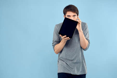 Emotional man with a tablet in the hands of a wireless device internet technology lifestyle blue background