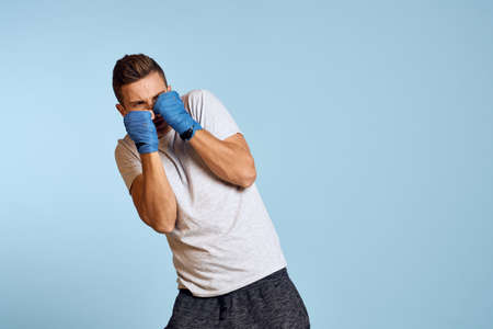 sporty man in blue boxing gloves and t-shirt on blue background practicing punches cropped view 写真素材