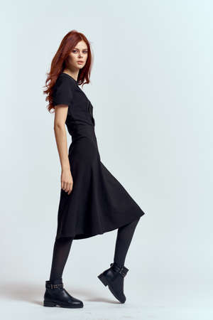 A woman in a black dress on a light background and pantyhose shoes red hair and pose in full growth