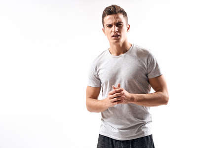 sporty man in white t-shirt on a light background gesturing with his hands cropped view Copy Space