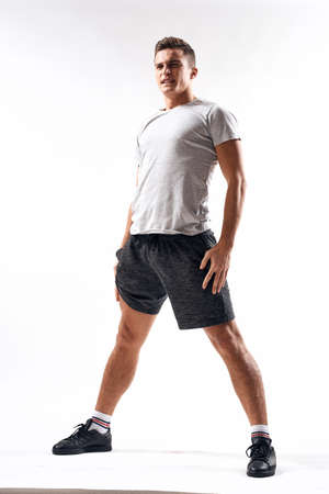 A sports man in shorts and a full-length T-shirt does exercises on a light background