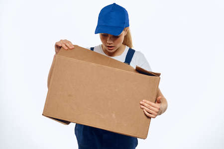 A woman in a working uniform with a box in the hands of a delivery service delivery service light background 版權商用圖片