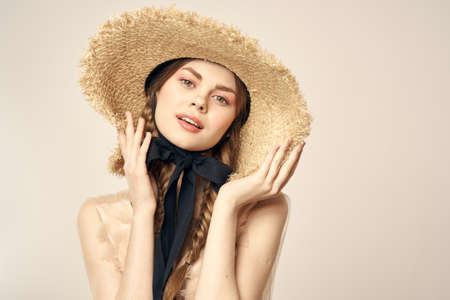romantic girl in beige dress and in straw hat with black ribbon emotions portrait of model cropped view