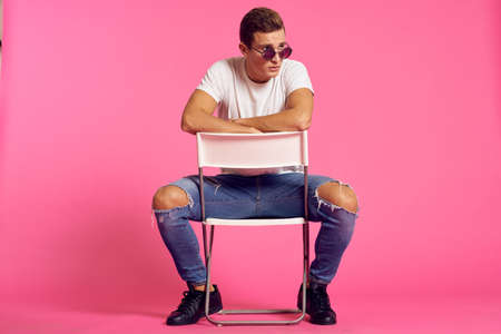 A man sits on a chair in a white t-shirt and jeans modern style pink isolated background